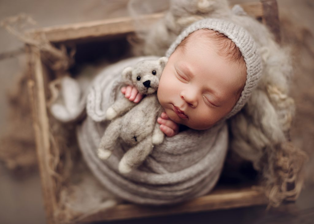 newborn baby boy holding a teddy bear